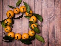 Świeży mandaryn lub tangerine z trzonami i liśćmi w postaci okręgu na brown drewnianej tło kopii przestrzeni Fotografia Stock