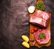 Świeży mięso na drewnianej desce z pomidorami, czosnkiem i pietruszką, opuszcza na ciemnym tle Obraz Royalty Free