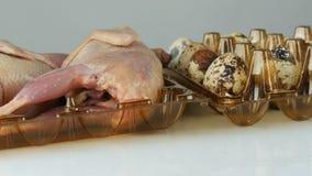Świeży mięso przepiórka w plastikowej brąz tacy obok przepiórek jajek na białym tle Kobiet ręki stawiają jajka wewnątrz zbiory