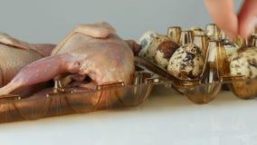 Świeży mięso przepiórka w plastikowej brąz tacy obok przepiórek jajek na białym tle Kobiet ręki stawiają jajka wewnątrz zdjęcie wideo