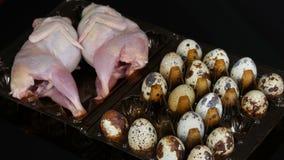 Świeży mięso przepiórka w plastikowej brąz tacy obok przepiórek jajek na czarnym tle Żeński ręka wp8lywy i stawiający zbiory wideo
