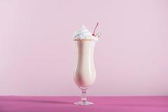 Świeży milkshake z śmietanką i wiśnią na wierzchołku w szkle zdjęcie stock
