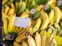 Świeży naturalny dojrzały banan z białym plakatem w rynku, Fotografia Royalty Free