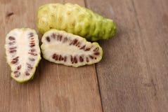 Świeży noni plasterek i noni owoc na liściu na drewnianym tle Fotografia Stock