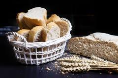 Świeży piec chleb i spikelets banatka na stole na czarnym tle Pokrojeni chlebów plasterki w koszu z banatką Wiejska piekarnia Zdjęcia Royalty Free