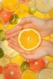 Świeży pomarańczowy plasterek w kobiet rękach Zdjęcia Stock