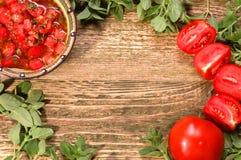 Świeży pomidorowy salsa z ziele na drewnianym stole Obrazy Stock