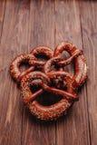 Świeży precel kropiący z sezamowymi ziarnami na drewnianym tle zdjęcia stock