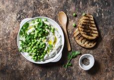 Świeży ricotta ser z zielonymi grochami, oliwa z oliwek, pieprzem i ziele na drewnianym tle, odgórny widok Zdrowej diety jedzenie Zdjęcie Royalty Free