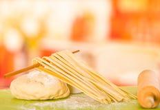 Świeży robić wysuszony spaghetti obwieszenie przez drewnianego kija lying on the beach na górze ciasta obok rollng szpilki zdjęcia stock