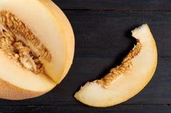 Świeży słodki żółty melon pokrajać na drewnianym czarnym tle Kawałek surowy organicznie melon na drewnianym zmrok powierzchni zak Zdjęcia Stock