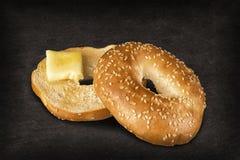 Świeży sezamowego ziarna bagel chleb z kawałkiem rozciekły masło obrazy stock