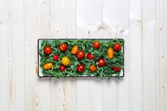 Świeży siekający przygotowany kale z żółtymi i czerwonymi czereśniowymi pomidorami na talerzu zdjęcia stock