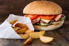 Świeży smakowity hamburger i dłoniaki na drewnie fotografia stock