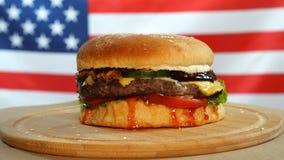 Świeży soczysty hamburger jest szybki wirować na USA flagi tle zbiory