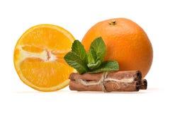 Świeży soczysty skład dojrzała pomarańcze, nowi liście, pomarańcz połówki i cynamonowi kije, obrazy royalty free