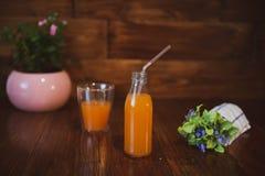 Świeży sok w butelce na drewnianym stole Zdjęcia Royalty Free