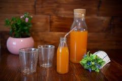 Świeży sok w butelce na drewnianym stole Fotografia Stock