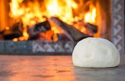 Świeży surowy ciasto dla pizzy lub chleba pieczenia na drewnianym stole przeciw Płonącej grabie wygoda nastroju pojęcie Obrazy Royalty Free