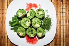 Świeży surowy karmowy naczynie Zieleni rolki gronowi liście z jarzynowym plombowaniem na bielu talerzu na słomie matują Fotografia Stock