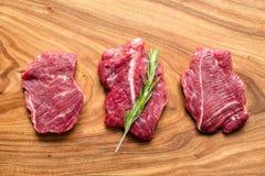 Świeży surowy mięso na ciapanie desce z rozmarynami, odgórny widok Zdjęcia Royalty Free