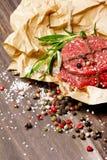 Świeży surowy stek z pieprzami, rozmaryny, sól na drewnianym tle Obrazy Stock
