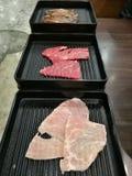 Świeży surowy wieprzowiny wołowiny plasterek dla grill porci na czarnej tacy który wzmacnia przedpole z plamy tłem, Ciency plaste fotografia royalty free