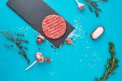 Świeży surowy wołowiny mięso z ziele i solą na turkusowym tle Zdjęcia Royalty Free