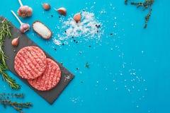 Świeży surowy wołowiny mięso z ziele i solą na turkusowym tle Zdjęcie Stock