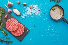 Świeży surowy wołowiny mięso z ziele i solą na turkusowym tle Fotografia Stock