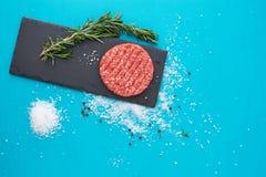 Świeży surowy wołowiny mięso z ziele i solą na turkusowym tle Zdjęcie Royalty Free