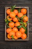 Świeży tangerine clementine z liśćmi na ciemnym drewnianym tle zdjęcia stock