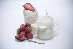 Świeży truskawkowy spada puszek w chełbotania mleko blisko deseru Obraz Stock