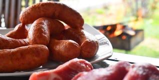 Świeży uncooked czerwony mięso, kiełbasy i klopsiki na drewnianym stole gotowym gotującym na plenerowym pożarniczym grillu, Grill obrazy stock