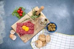 Świeży wołowiny mięso w forcemeat, na drewnianej desce Surowi jajka i pomidory są mali Ziele dla gotować i round babeczek Na szar obrazy stock