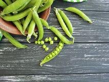 Świeży zielonego grochu naczynie ręcznikowy żniwo składnika lata adry odżywki jarosz na czarnym drewnianym tle obraz royalty free