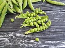 Świeży zielonego grochu naczynie ręcznikowy jarosz na czarnym drewnianym tle zdjęcia royalty free