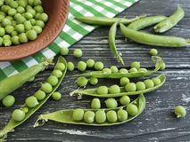 Świeży zielonego grochu naczynie ręcznikowy składnik odżywki jarosz na czarnym drewnianym tle fotografia stock