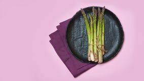 Świeży zielony asparagus na czarnym ceramicznym naczyniu, fiołkowej bieliźnianej pielusze i menchii tle, zdjęcie stock