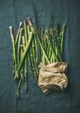 Świeży zielony asparagus w rzemiosło papierowej torbie nad popielatym płótnem Fotografia Royalty Free