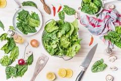 Świeży zielony szpinak opuszcza w colander na białym kuchennego stołu tle z kulinarnymi składnikami zdjęcie stock