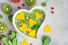 Świeży zielony szpinaka smoothie puchar z mango i kiwi Obrazy Stock