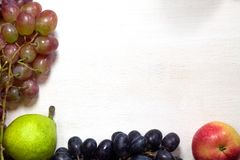 Świeżych owoc winogrona, bonkreta i jabłko na drewnianych deskach, obramiają tło zdjęcia royalty free