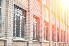 Świecenie słońce i budynek z metali barami na Windows zdjęcia stock