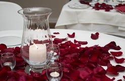 Świeczka I Różanych płatków Centrum kawałek Na stole Obrazy Stock