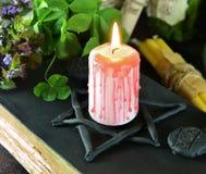 Świeczka na czarnej magii książce z koniczyną Fotografia Royalty Free