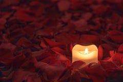 Świeczka na róża płatków tle Zdjęcia Stock