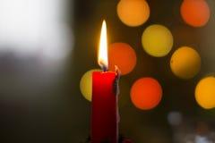 Świeczka płomień z bokeh choinki światłami Zdjęcia Royalty Free