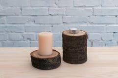 Świeczka stojak na drewnianej bazie na tle biały ściana z cegieł Obraz Royalty Free