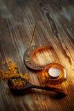 Świeczka w żółtym szklanym candlestick z lotniczymi bąblami inside, kadzidłowy kija dymienie, rybiego oleju kapsuły Obraz Royalty Free